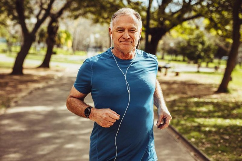 Older man jogging with headphones on